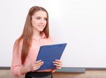 Lächelnde Studentin, die mit Ordner steht Stockfotografie