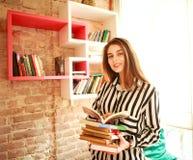 Lächelnde Studentin mit Büchern in der Bibliothek stockfotos