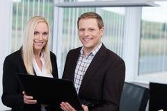 Lächelnde Teilhaber, die einen Laptop verwenden Stockfotografie