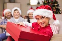 Lächelnde Tochter, die Geschenk mit ihrer Familie hinten hält Stockbild