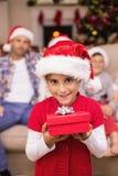 Lächelnde Tochter, die Geschenk vor ihrer Familie hält Stockfotos
