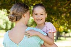 Lächelnde Tochter, die ihre Mutter am Park umfasst Lizenzfreies Stockfoto