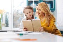 Lächelnde Tochterlesung mit ihrer Mutter Lizenzfreies Stockfoto