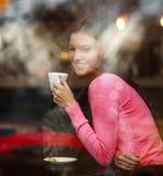 Lächelnde träumerische durchdachte Frau im Restaurant mit dem Tasse Kaffee, froh heraus schauend, Ansicht durch Fenster mit Refle lizenzfreie stockfotos