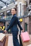 lächelnde tragende Einkaufstaschen und Schauen der attraktiven Geschäftsfrau stockfoto