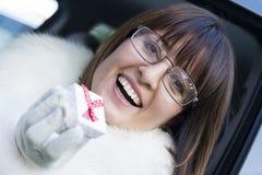 Lächelnde tragende Gläser der Frau, die eine Geschenkbox halten Stockfotos