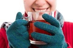Lächelnde tragende Handschuhe und Halten der Frau des heißen Tees lizenzfreie stockbilder