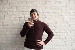 Lächelnde tragende Kappe des jungen Mannes, die Smartphone in seiner Hand untersucht Lizenzfreie Stockfotografie