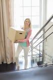 Lächelnde tragende Pappschachtel der Frau, beim hochschieben am neuen Haus tritt Lizenzfreie Stockfotos