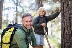 Lächelnde tragende Rucksäcke des Vaters und des Sohns beim Wandern im Wald Lizenzfreies Stockbild
