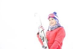Lächelnde tragende Skis der jungen Frau im Schnee Stockfoto