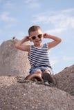 Lächelnde tragende Sonnenbrille und Weste des Kleinkindes, die auf konkretem Wellenbrecher sitzen Lizenzfreies Stockfoto
