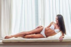 Lächelnde tragende weiße Wäsche der dünnen jungen Brunettefrau, die auf der Couch in camera schaut zuhause im hellen Raum über li lizenzfreies stockfoto