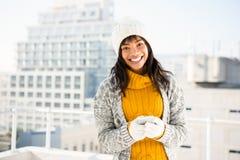 Lächelnde tragende Winterkleidung der Frau und Schreiben an ihrem Telefon lizenzfreie stockfotos