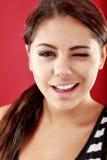 Lächelnde und blinzelnde Frau Stockfotografie