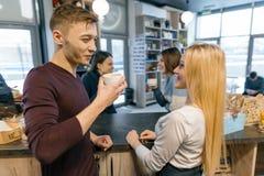 Lächelnde und Unterhaltungsbarista Funktion der Junge an der Kaffeestube hinter dem Tresen entgegengesetzt mit Schale frischem Ka lizenzfreie stockfotografie