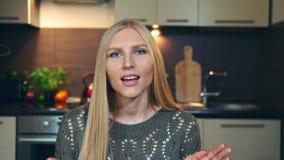 Lächelnde und wellenartig bewegende Hand der hübschen Frau Reizende junge weibliche lächelnde und schauende Kamera beim vlog Publ stock video footage