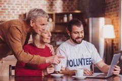 Lächelnde unterrichtende Pensionäre des Mannes, wie man einen Laptop benutzt lizenzfreie stockbilder