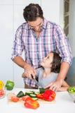 Lächelnde unterrichtende Tochter des Vaters, zum des Gemüses zu schneiden Lizenzfreie Stockfotografie