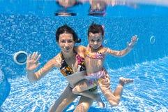 Lächelnde Unterwasserfamilie im Swimmingpool Lizenzfreies Stockbild