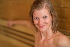 Lächelnde verschwitzte Frau in der Sauna lizenzfreies stockfoto