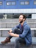 Lächelnde Versenden von SMS-Nachrichten des jungen Mannes auf Mobiltelefon Stockfoto