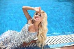 Lächelnde vorbildliche Aufstellung des blonden Mädchens der Schönheitsmode im Partykleid LY Stockfoto