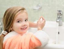 Lächelnde waschende Hände des kleinen Mädchens im Badezimmer Stockbild