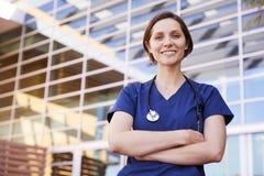 Lächelnde weiße weibliche Gesundheitswesenarbeitskraft draußen, Taille oben stockfoto