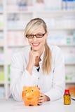 Lächelnde weibliche Apothekerhaltungen mit einem Sparschwein lizenzfreie stockfotos