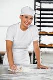 Lächelnde weibliche Bäcker-Cleaning Flour From-Tabelle Lizenzfreie Stockbilder