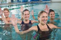 Lächelnde weibliche Eignungsklasse, die Aquaaerobic tut Stockfoto