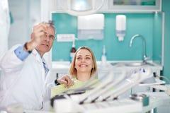 Lächelnde weibliche Frau mit dem Zahnarzt, der zahnmedizinischen Schnappschuß betrachtet Lizenzfreies Stockbild