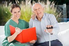 Lächelnde weibliche Krankenschwester And Senior Man mit Buch Stockfotografie