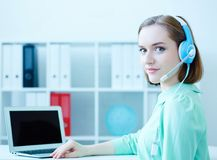Lächelnde weibliche Kundenbetreuung rufen den Betreiber an, der an der Büroarbeitsplatzhalben drehung sitzt, die in camera Porträ stockfotografie