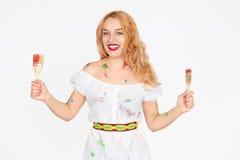 Lächelnde weibliche Malerholdingbürsten mit beiden Händen Lizenzfreies Stockfoto