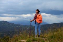 Lächelnde weibliche Stellung auf Berg schaut auf dem links Stockbild