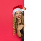 Lächelnde Weihnachtsfrau, die auf Plakat zeigt Stockbild