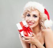 Lächelnde Weihnachtsfrau in Santa Hat mit Weihnachtsgeschenk auf Grau Stockfotos