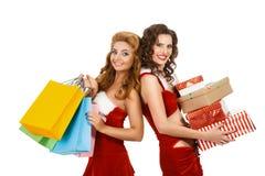 Lächelnde Weihnachtsfrauen, die Geschenk und bunte Pakete halten Stockfotos