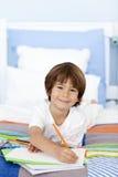 Lächelnde Zeichnung des kleinen Jungen im Bett Lizenzfreie Stockfotografie