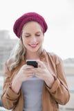 Lächelnde zufällige blonde Versenden von SMS-Nachrichten draußen Lizenzfreie Stockfotos