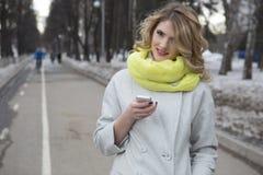 Lächelnde zufällige blonde Versenden von SMS-Nachrichten draußen Stockbilder