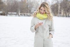 Lächelnde zufällige blonde Versenden von SMS-Nachrichten draußen Stockfoto