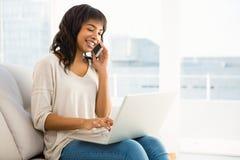 Lächelnde zufällige Frau, die einen Telefonanruf bei der Anwendung des Laptops hat Stockfoto