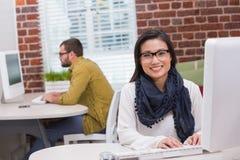 Lächelnde zufällige junge Frau, die Computer verwendet Lizenzfreie Stockfotos