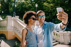 lächelnde zwischen verschiedenen Rassen Paare in der Sonnenbrille, die selfie auf Smartphone nimmt lizenzfreies stockfoto