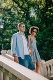 lächelnde zwischen verschiedenen Rassen Paare in der Sonnenbrille, die die Treppe hinunter geht stockfotos