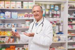 Lächelnder älterer Doktor, der Medikation zeigt lizenzfreie stockfotografie