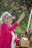 Lächelnder älterer Frauen-Anstrich Stockfotografie